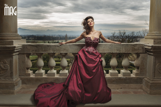 Lucia Rossi con vestito rosso elegante che posa a braccia distese nel terrazzo e panorama della alta valle tiberina