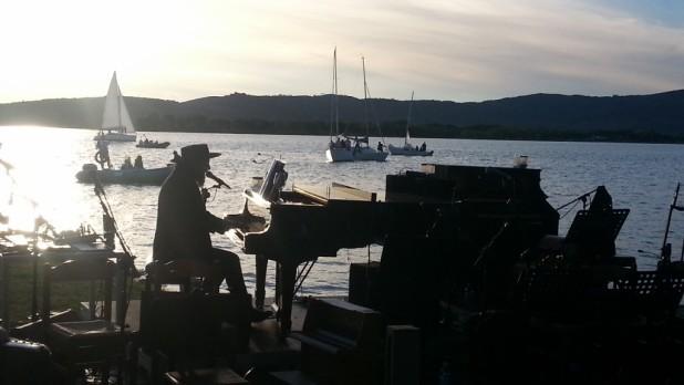 Vinicio Capossela mentre suona il pianoforte nel paesaggio del lago Trasimeno