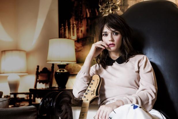 Carmen Consoli seduta su una poltrona con la chitarra a fianco