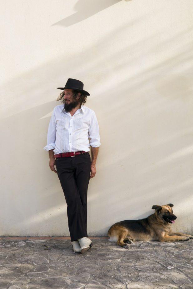 Vinicio Capossela posa appoggiato al muro con un cane