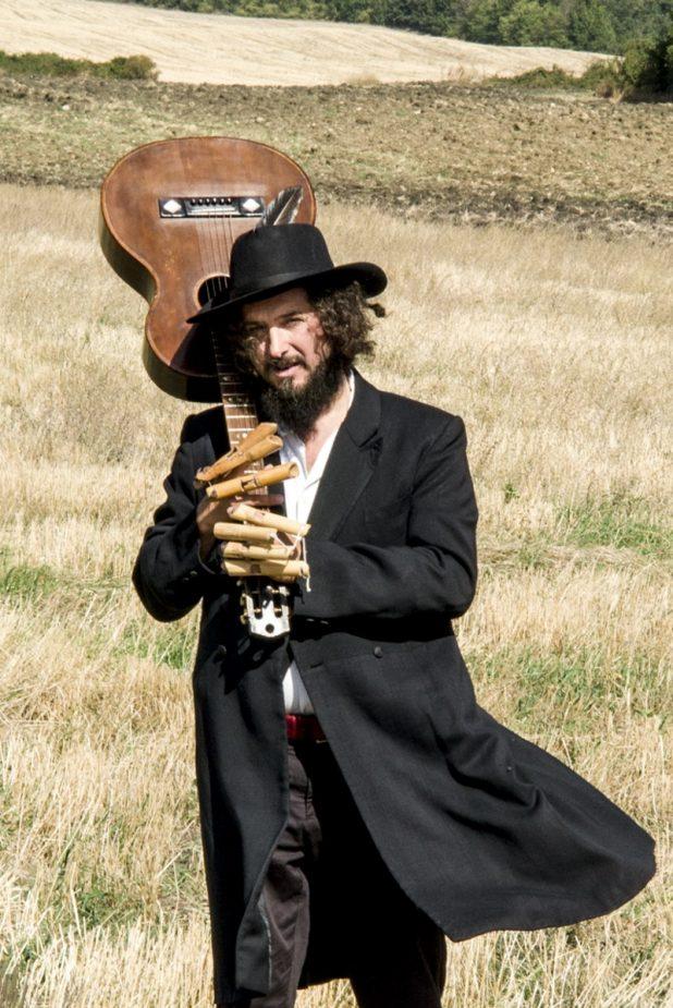 Vinicio Capossela ritratto con la chitarra mentre cammina su un campo di grano
