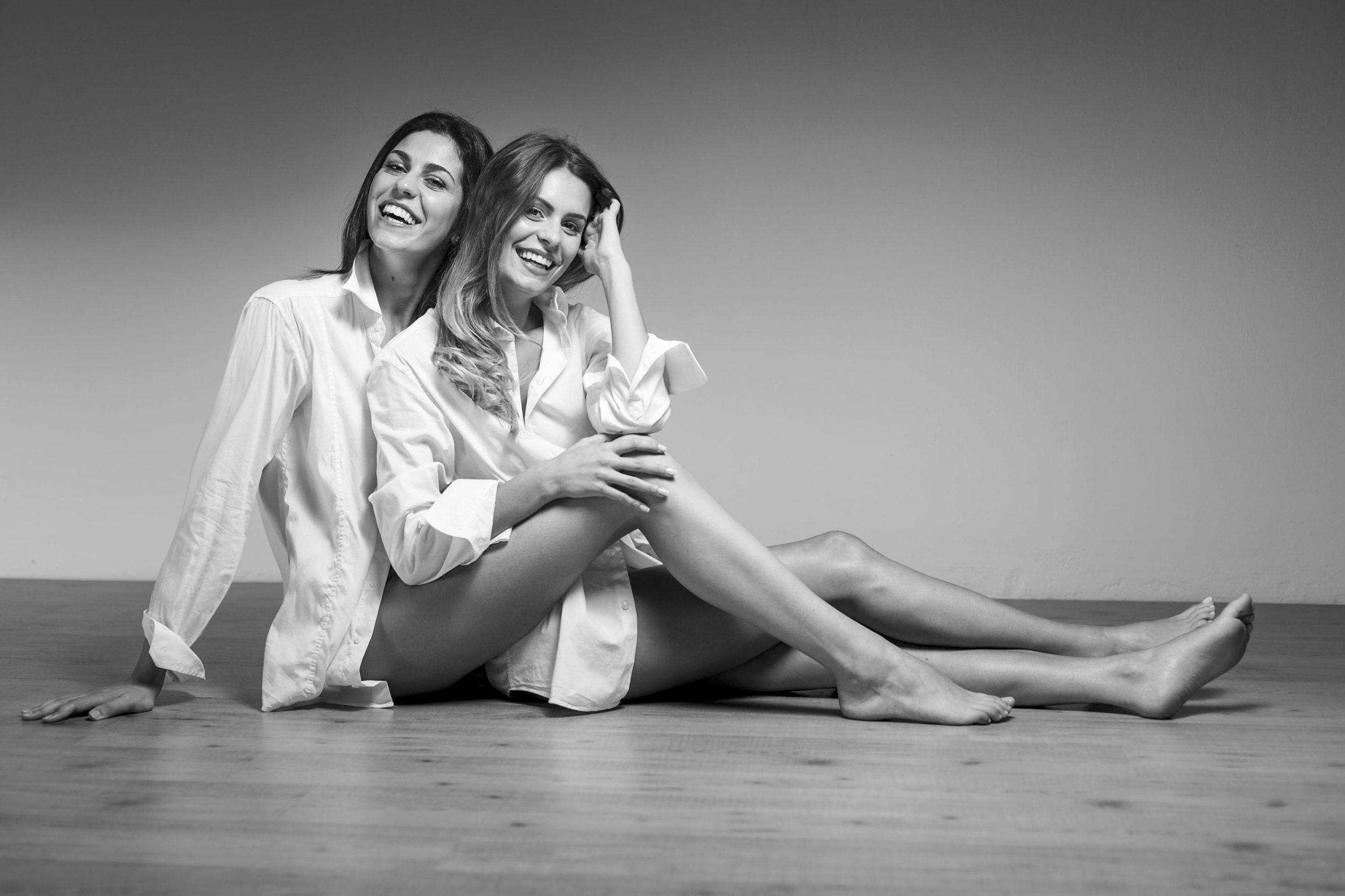 Arianna Torrioli e Sofia Pompei sorridono sedute in una foto in studio con camicie bianche e gambe nude