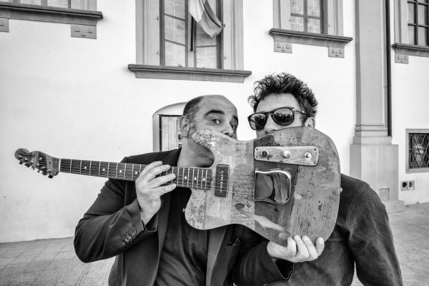 Elio Germano scherza con Teho Teardo nascondendosi dietro la chitarra