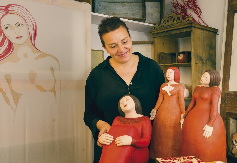 Elena Merendelli sorride accanto alle sue creazioni nella bottega/laboratorio di Anghiari