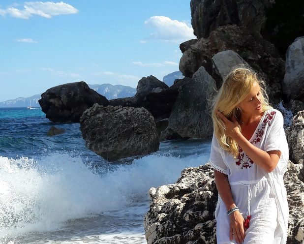 Ritratto di Cristina Crisci al mare mentre si aggiusta i lunghi capelli biondi