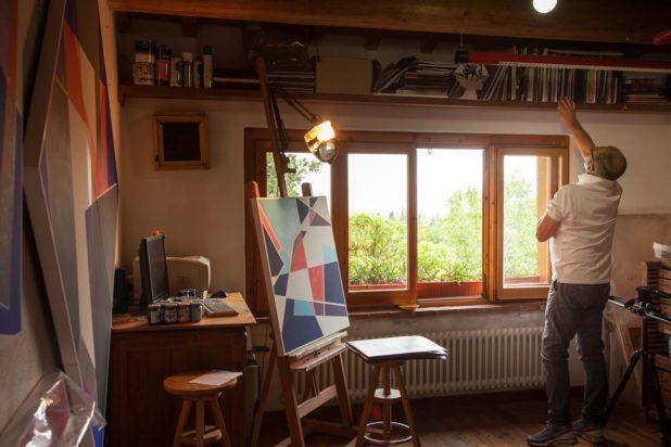 Fabio Mariacci cerca un libro nel suo laboratorio artistico