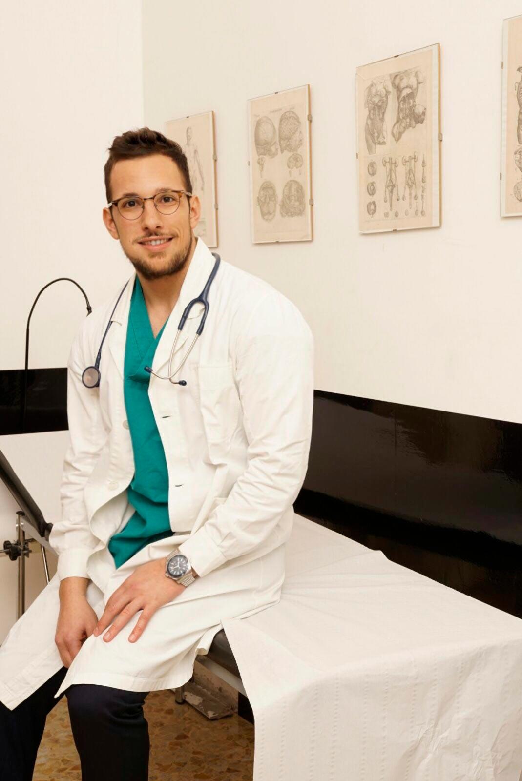 Giulio Giammarioli sorride con il camice seduto sul lettino del suo studio medico