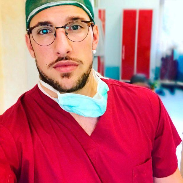 ritartto di Giulio Giammarioli con camice rosso nello studio di medicina estetica
