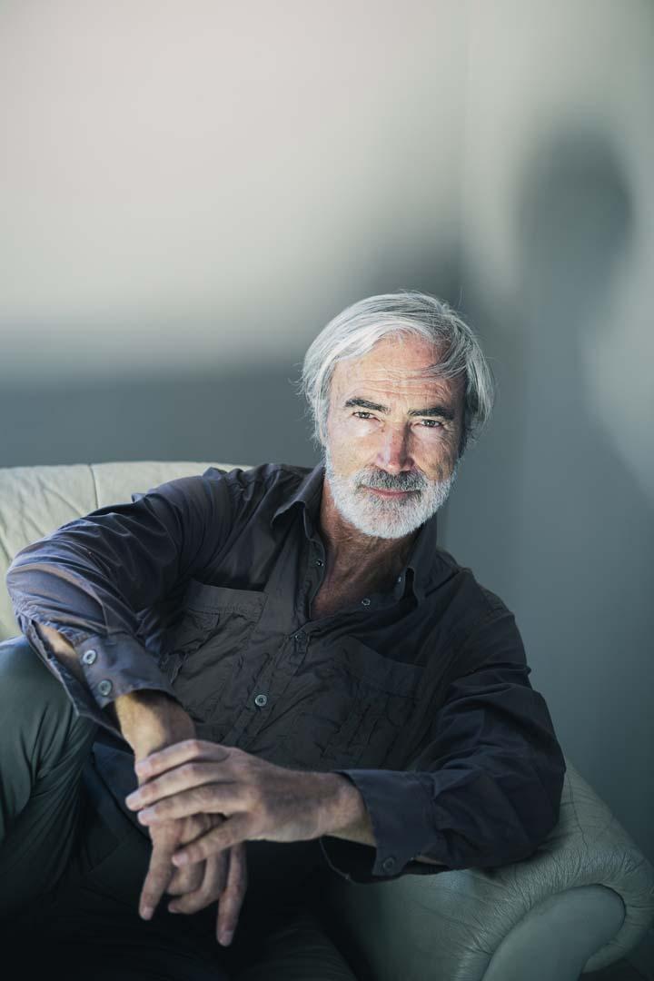 ritratto di Massimo Gradini intenso con luce morbida, seduto sul sofa