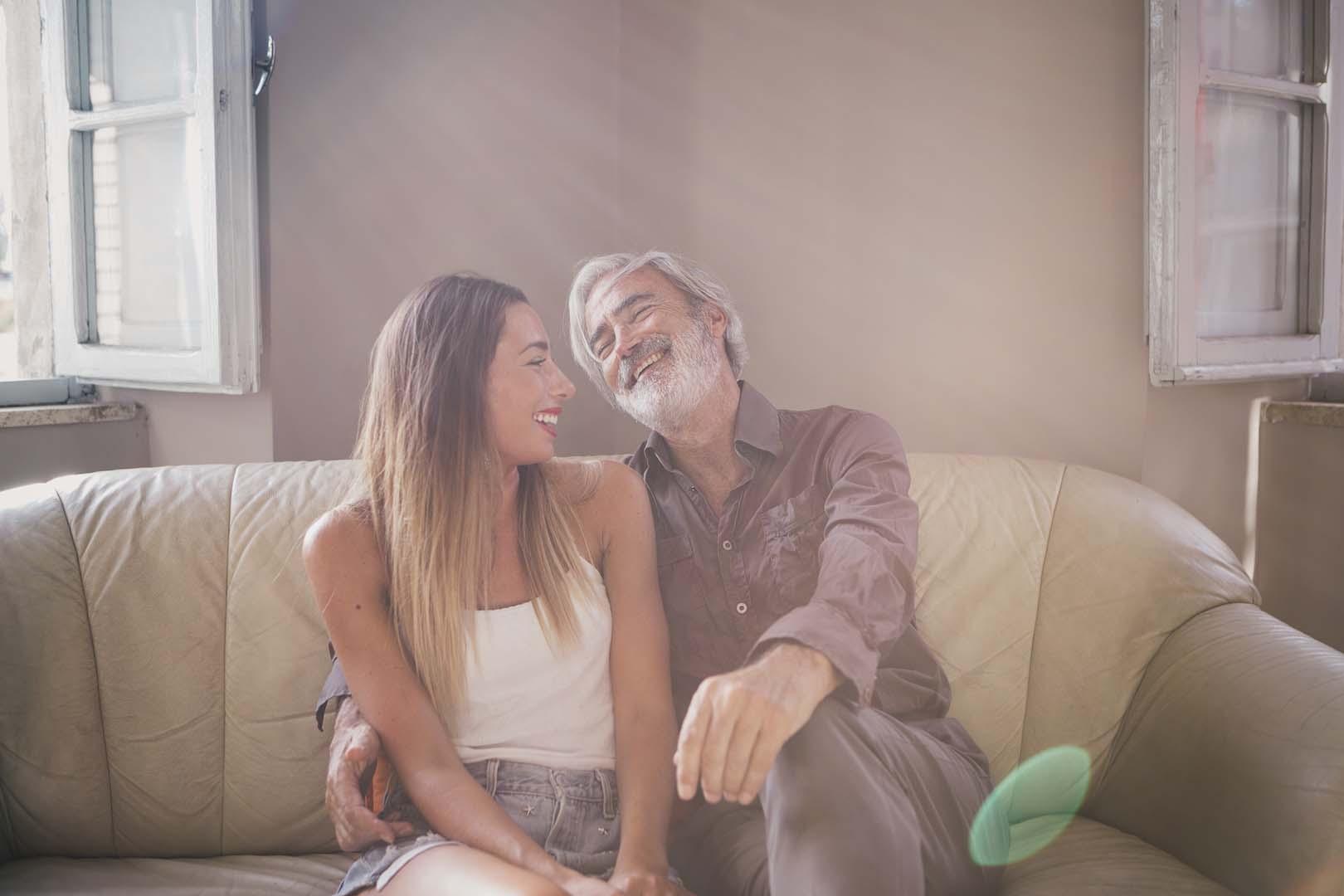 Massimo Gradini e Monica Bartolucci sorridono insieme seduti sul divano in controluce