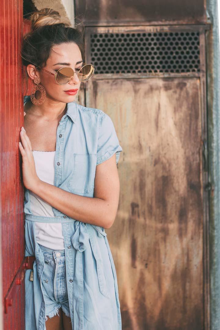 Monica Bartolucci fotografata con grandi occhiali circolari e camicia aperta
