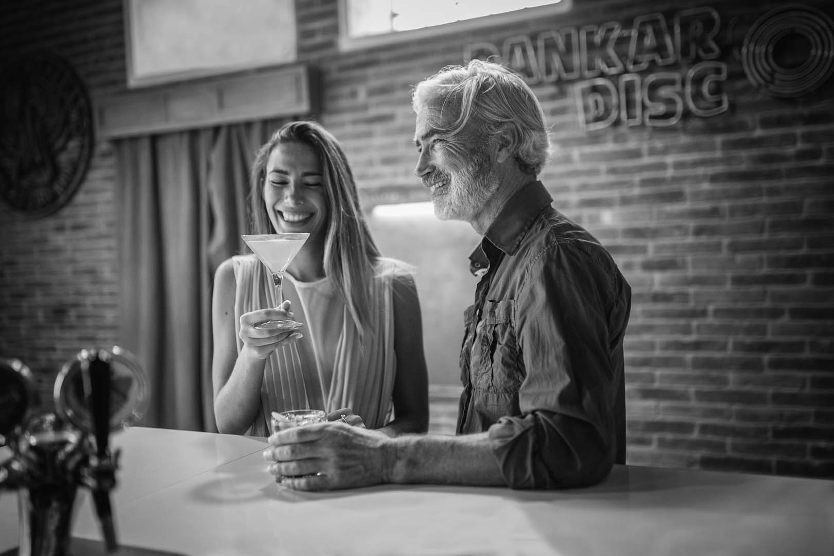 Massimo Gradini e Monica Bartolucci bevono seduti al bancone in un ritratto in bianco e nero