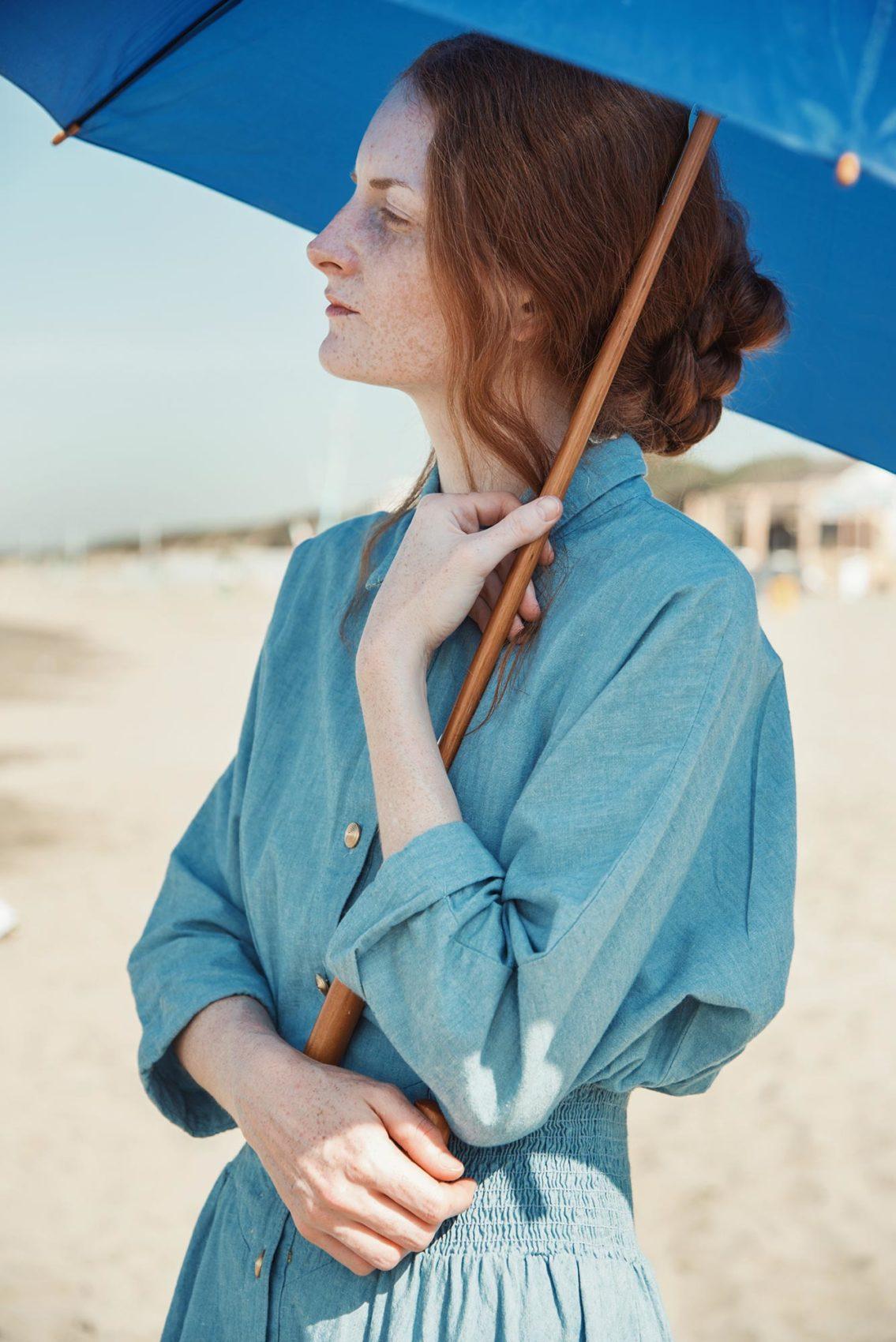 """Giulia Beltrame con l'ombrello in spiaggia nel video """"Falling Upwards"""" guarda verso il mare"""