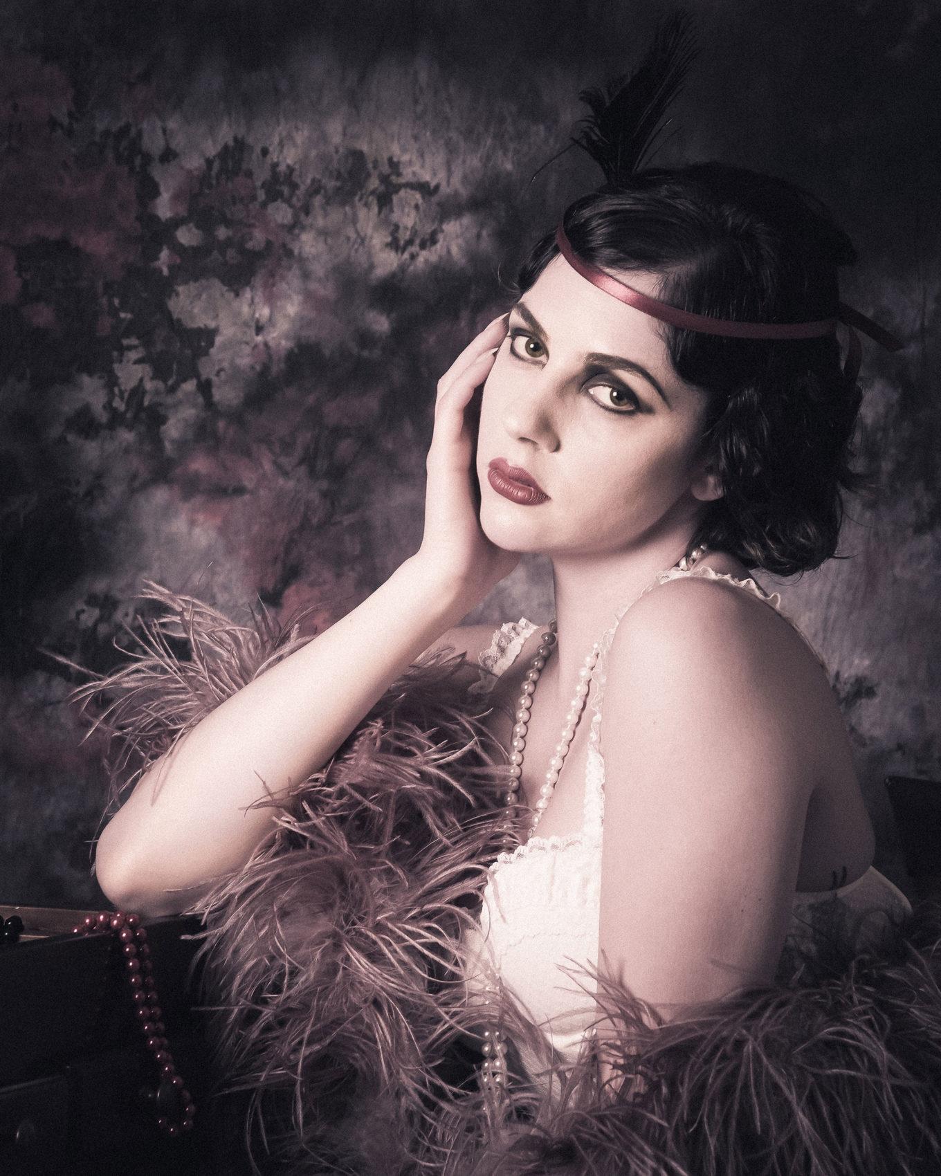 Jessica Frascarelli in posa burlesque porta la mano al viso e posa con le sue piume