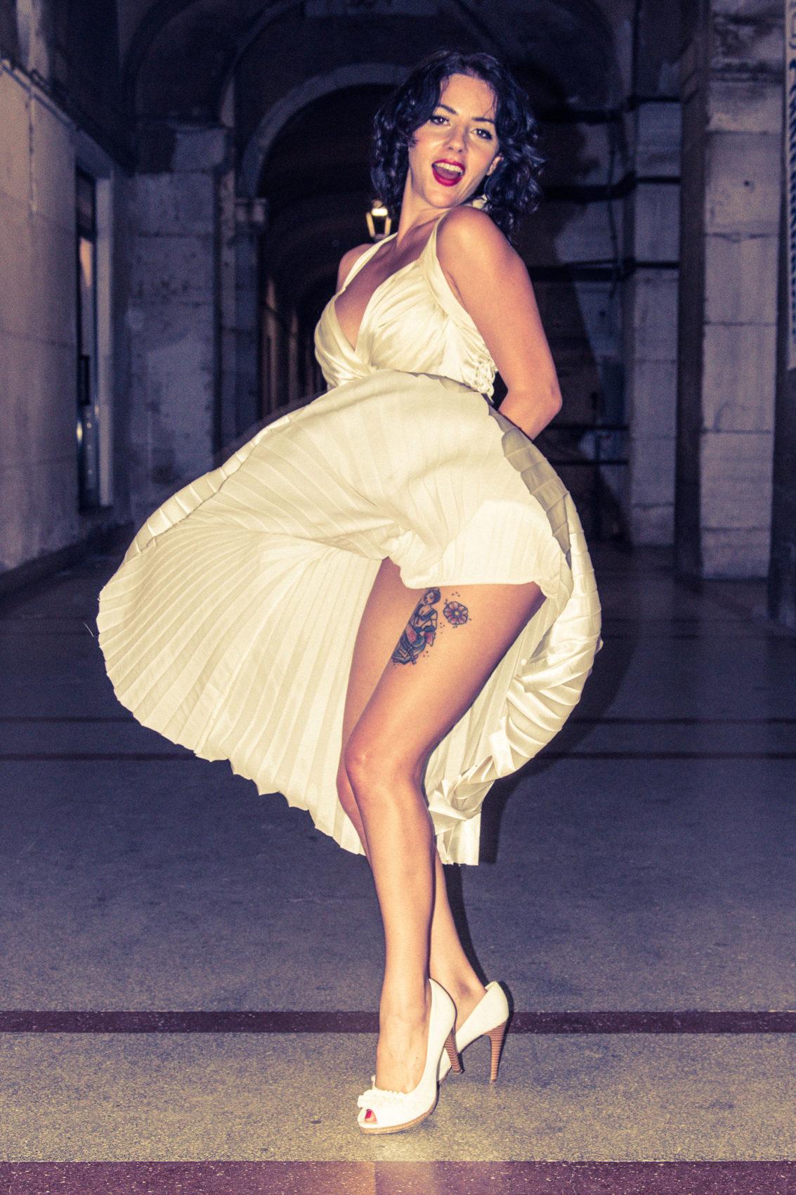 Jessica Frascarelli come Marilyn Monroe in abito bianco alzato dal vento mostra le gambe