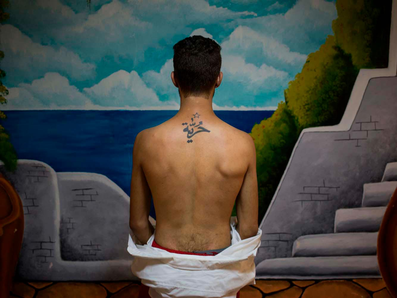 A young actor, working with the Fani Raghman Ani group, an association defending human rights in Tunisia, showing a tattoo on his back, saying 'freedom' in Arabic.