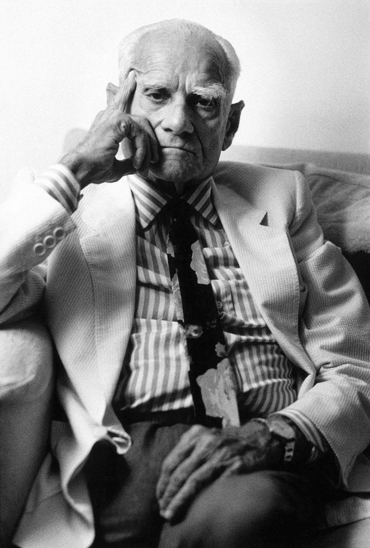 Ritratto di Alberto Moravia seduto sul divano con la mano sul volto