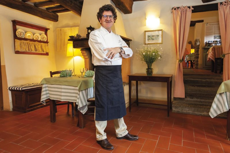 Pier Luigi Manfroni sorride a braccia conserte nel suo ristorante in Toscana